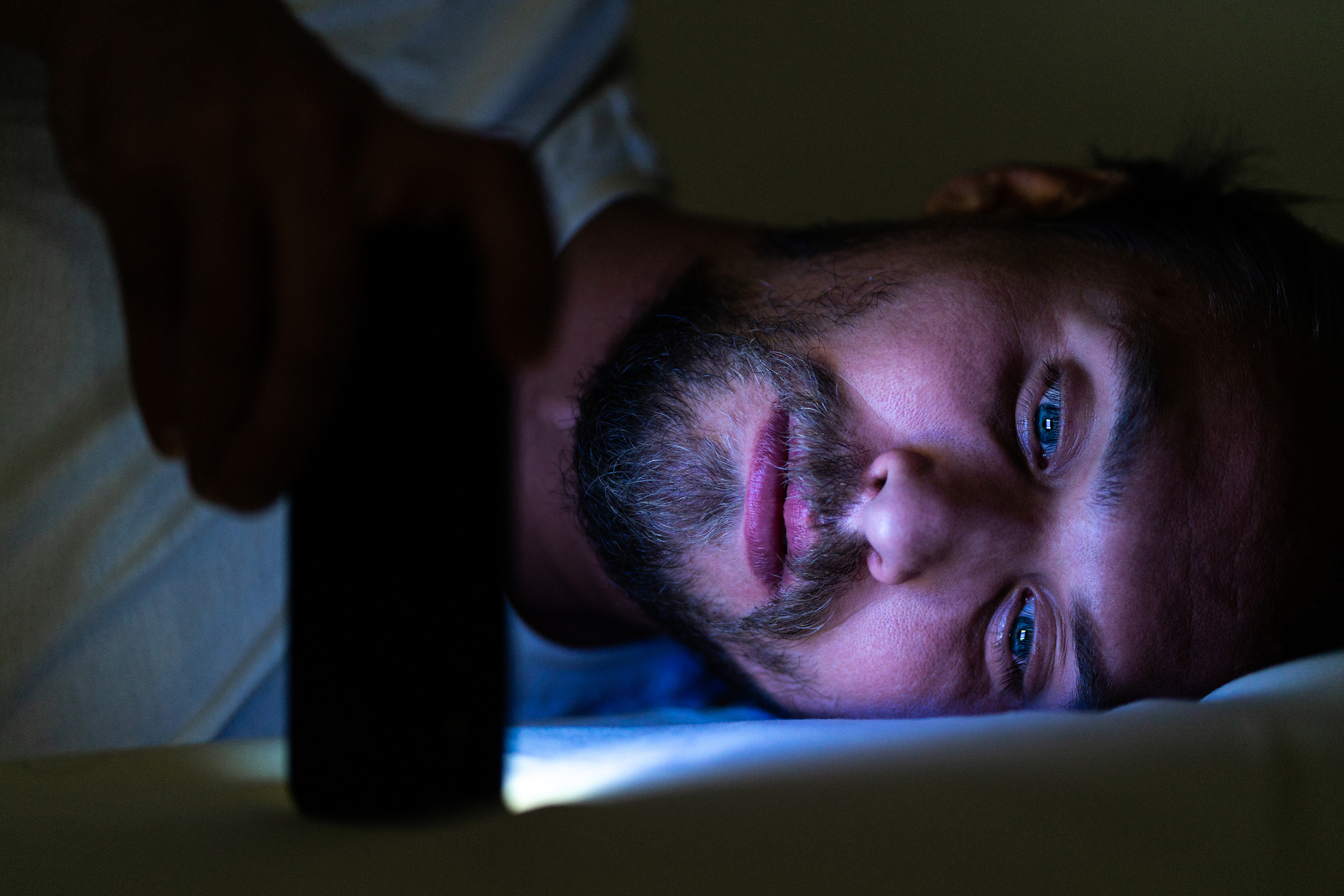 Sleepless man in bed holding his mobile phone